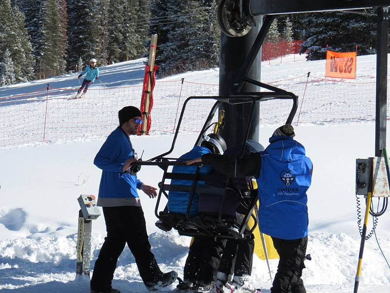 lift operators loading skiers in a chair
