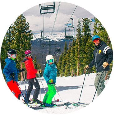 4 skiers standing at the top of the hill