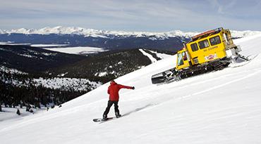 Snowboarder and snowcat heading down Chicago Ridge