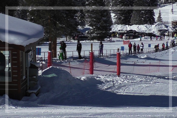 people riding the magic carpet up to the top of the beginner area