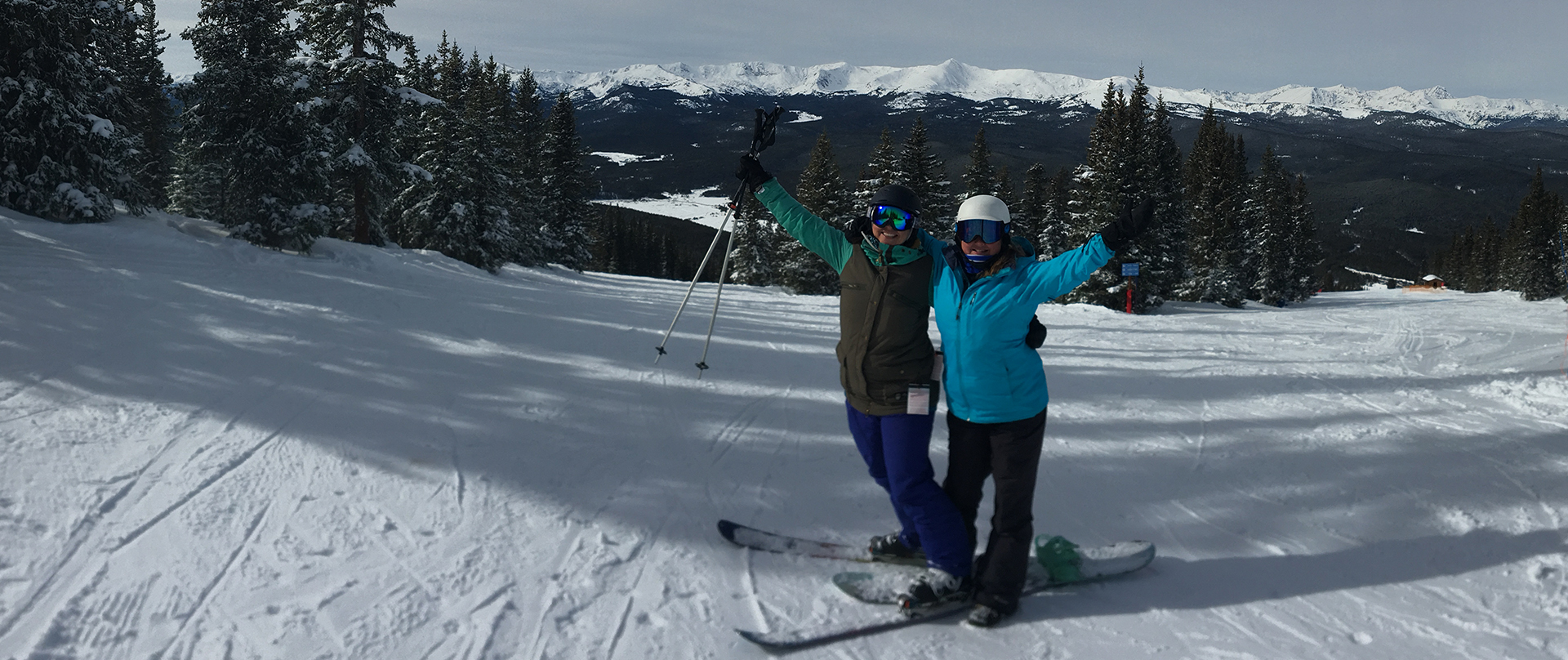 2 people posing on the top of a ski trail